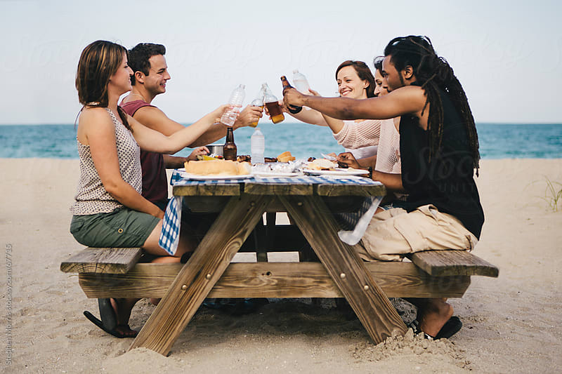 Friends Eating Picnic at the Beach by Stephen Morris for Stocksy United