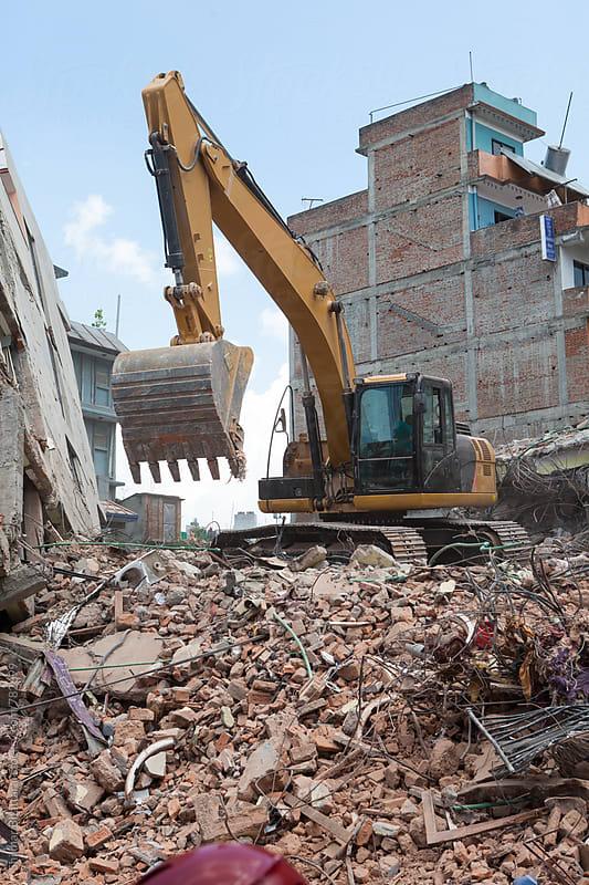 An excavator clearing off debris. by Shikhar Bhattarai for Stocksy United