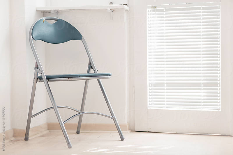 A chair by the balcony door. by Nabi Tang for Stocksy United