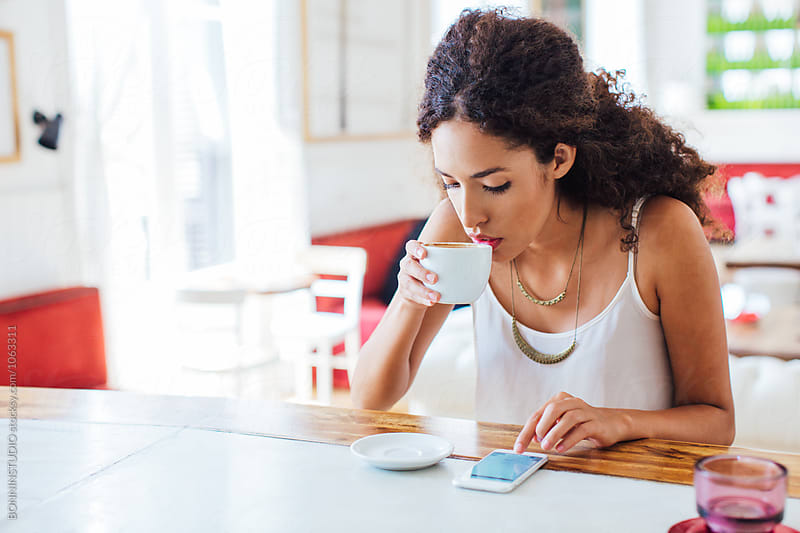 Young businesswoman using phone whilst having breakfast in a coffee bar.  by BONNINSTUDIO for Stocksy United