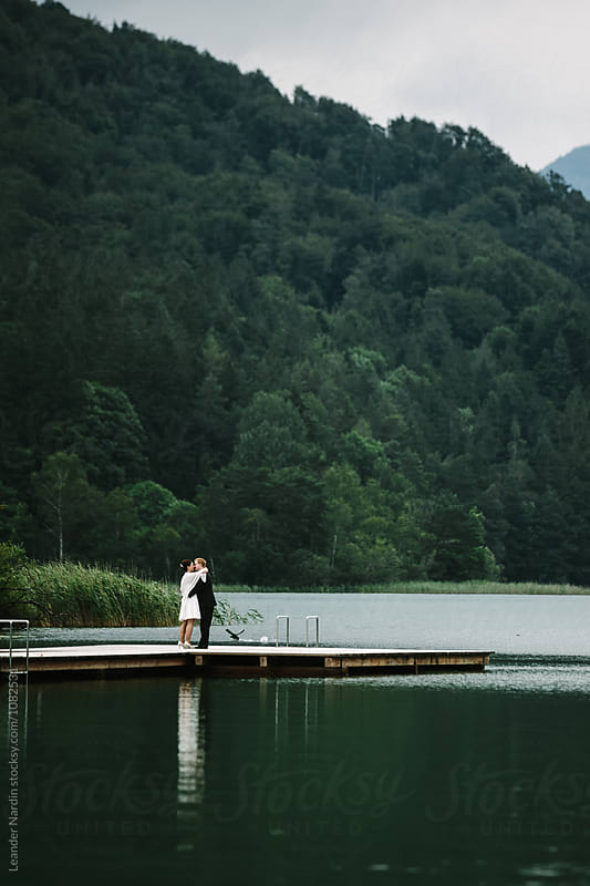hugging bridal couple on a jetty at a a lake by Leander Nardin for Stocksy United
