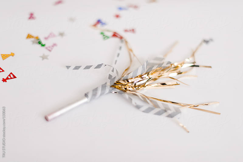 Party favor with confetti and gold streamers on white background. by TRU STUDIO for Stocksy United