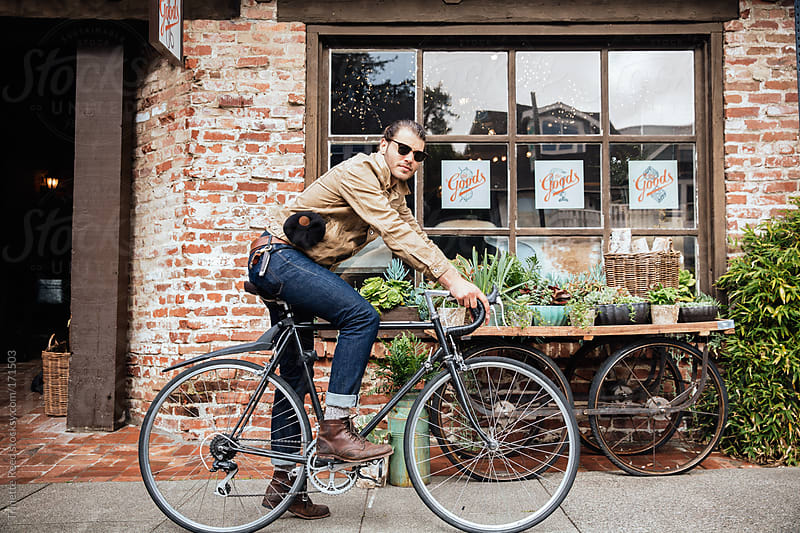 Hipster millennial on bike in front of store by Trinette Reed for Stocksy United