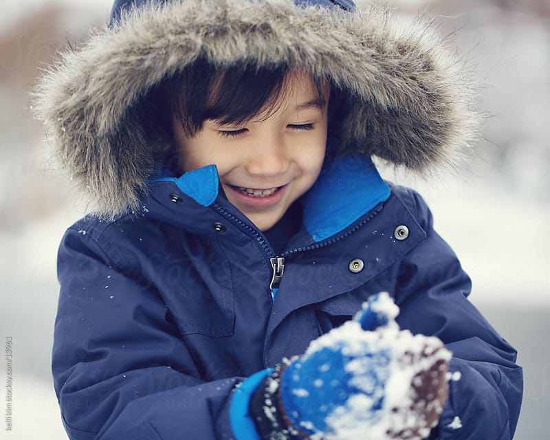 A young child makes a snowball by kelli kim for Stocksy United