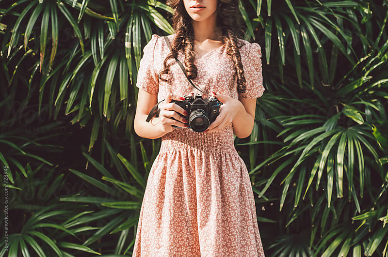 Beautiful girl with curly hair holds an analog camera by Jovo Jovanovic for Stocksy United