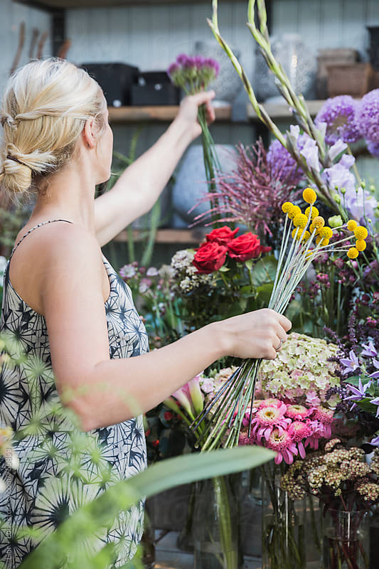 Blond woman arranging flowers in a flower shop by Lior + Lone for Stocksy United