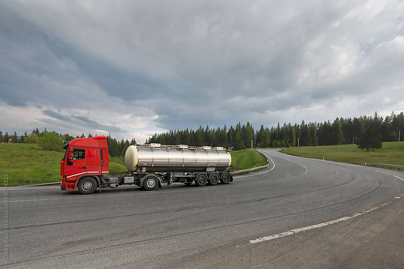 Gas tank truck driving on a cross-country road by RG&B Images for Stocksy United