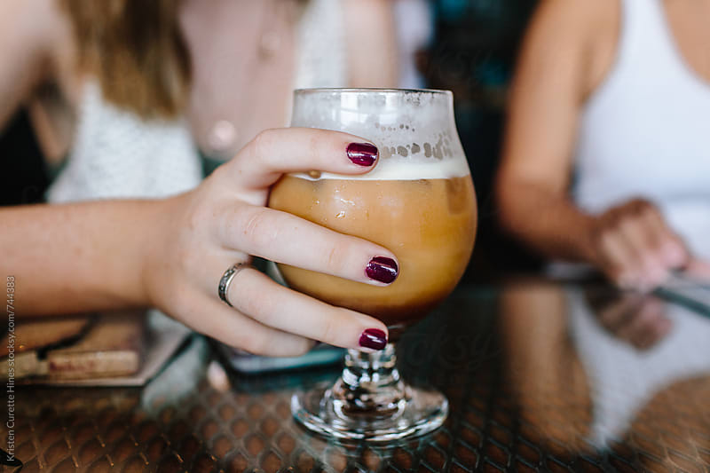Close up of a woman holding an iced vanilla latte by Kristen Curette Hines for Stocksy United