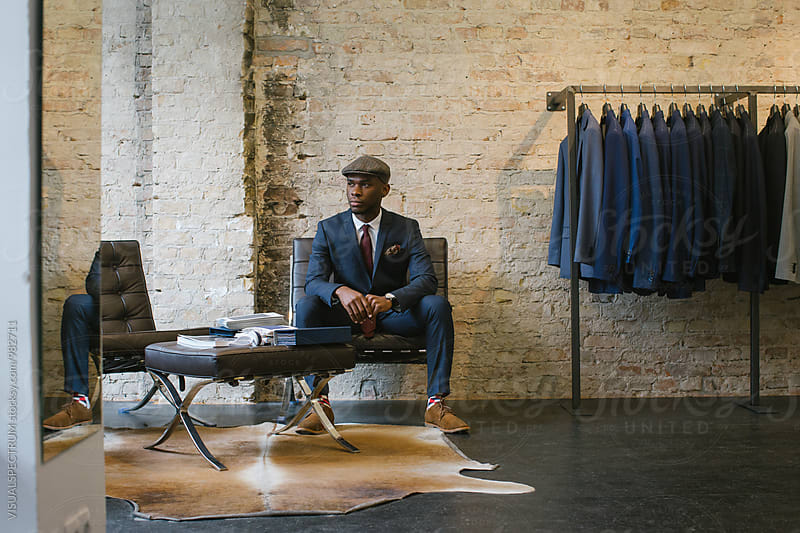 Elegant Young Black Man in Blue Suit Sitting in Upscale Men's Fashion Store by VISUALSPECTRUM for Stocksy United