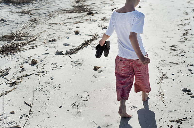 Boy walks along sandy beach holding his shoes in his hands by Cara Slifka for Stocksy United