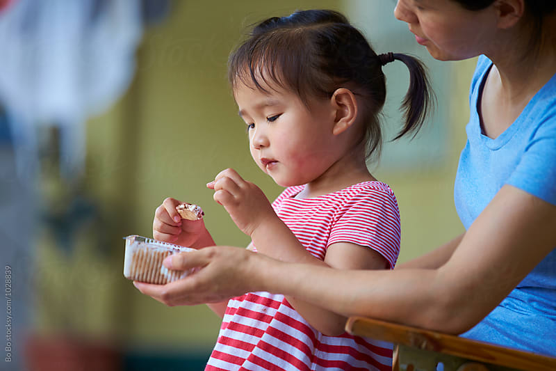 little asian girl eating ice cream  by Bo Bo for Stocksy United
