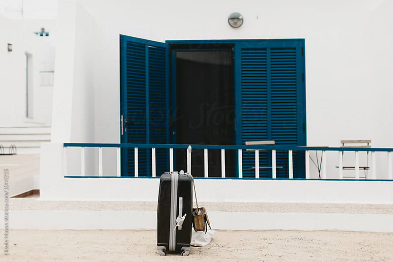 suitcase sitting outside of white home on island by Nicole Mason for Stocksy United