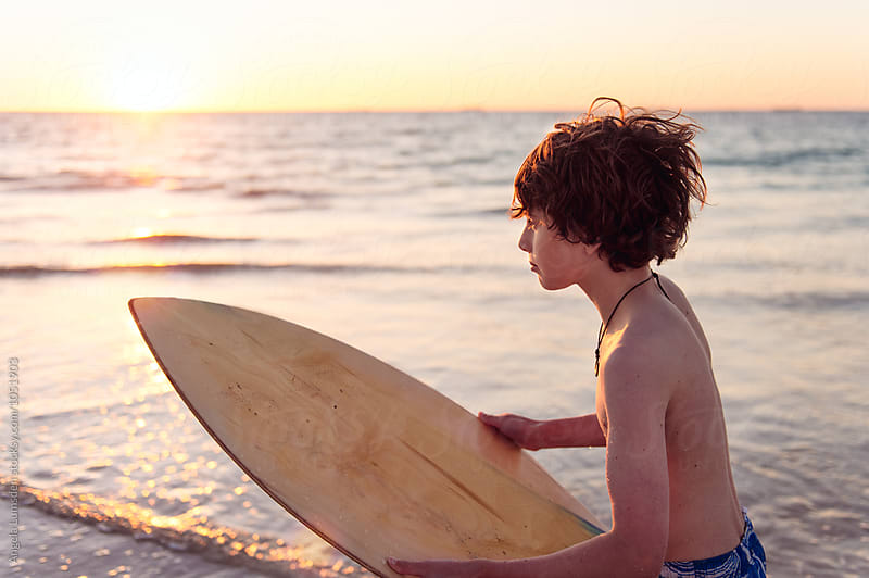 Close up of a young teenage boy at the beach with a skim board by Angela Lumsden for Stocksy United