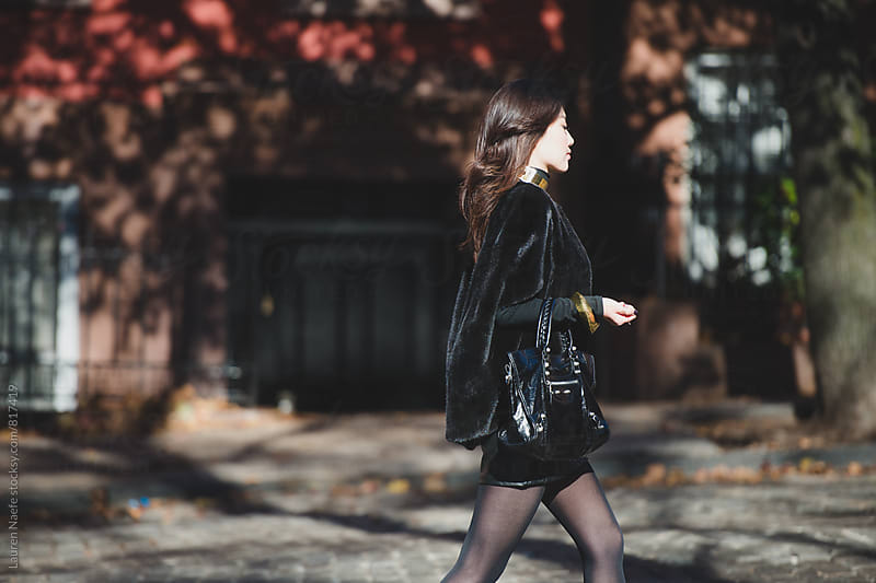 Attractive young woman crossing the street by Lauren Naefe for Stocksy United