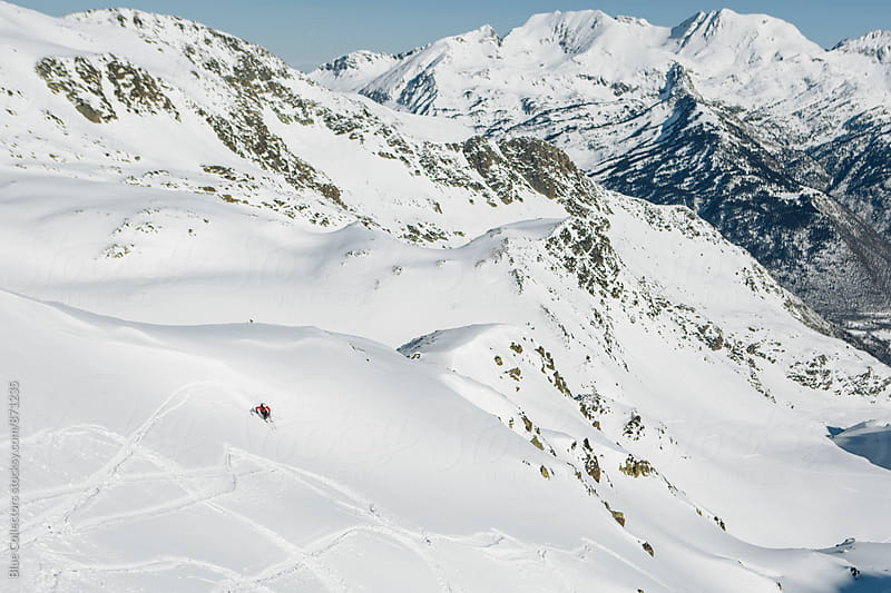 Male skier down the mountain in a beautiful valley by Jordi Rulló for Stocksy United