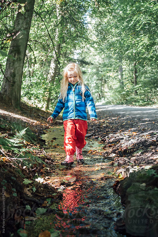 People: Girl walking in a little creek with rubber boots on by Ina Peters for Stocksy United