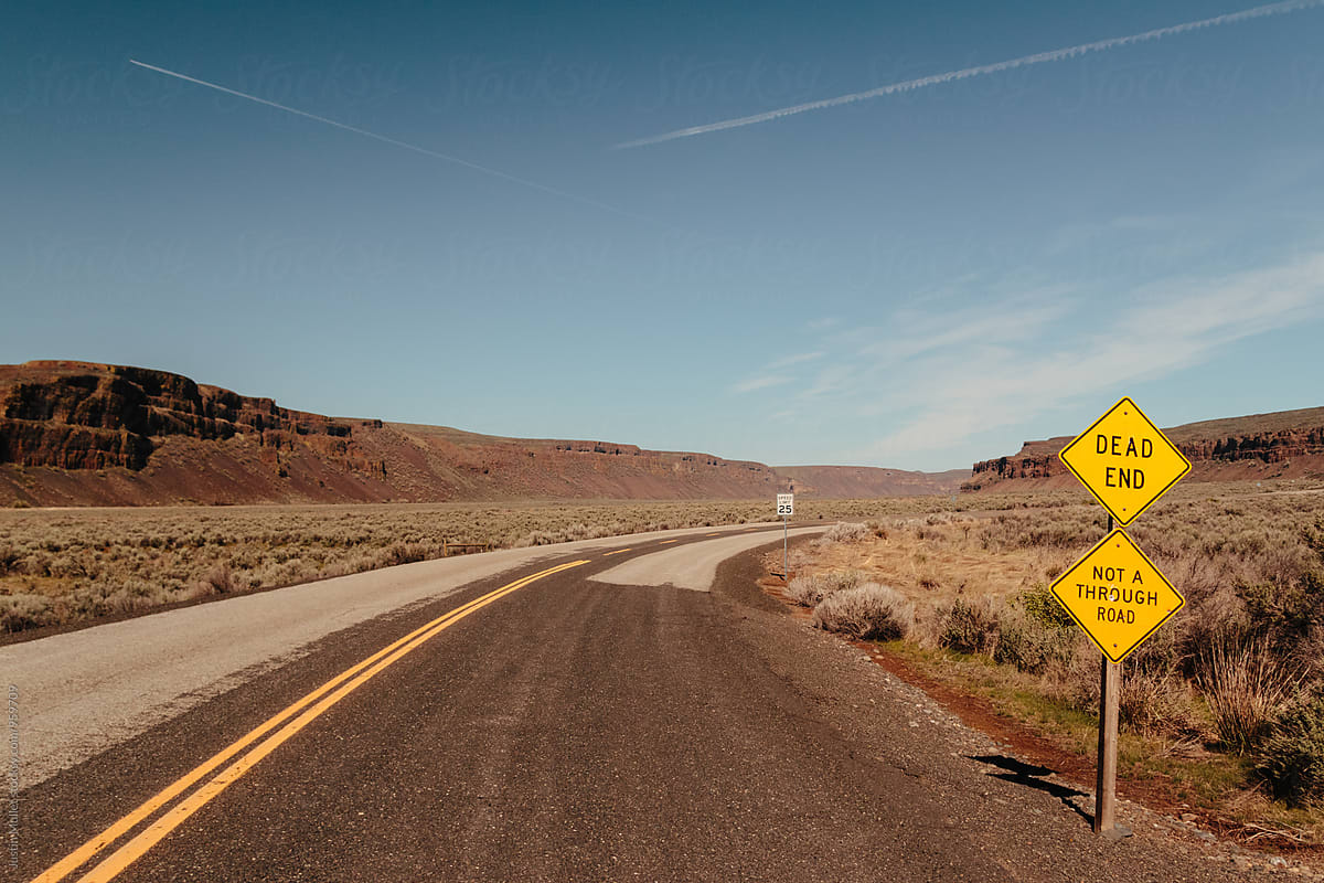 Dead end road in the desert on a clear morning by Justin Mullet