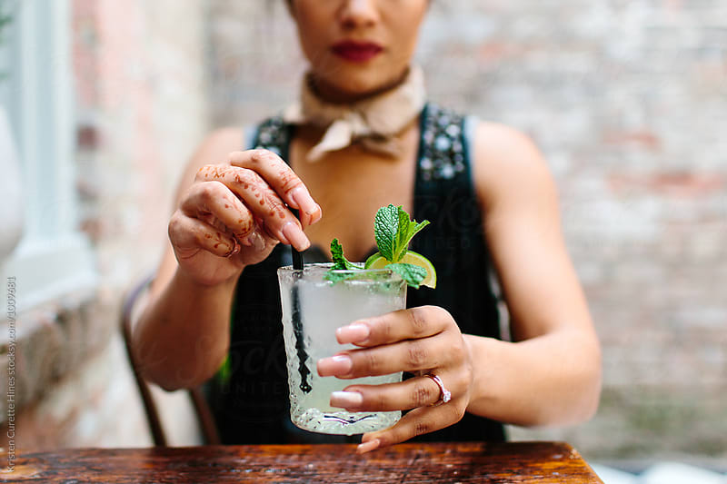 A woman drinking a refreshing mojito  by Kristen Curette Hines for Stocksy United