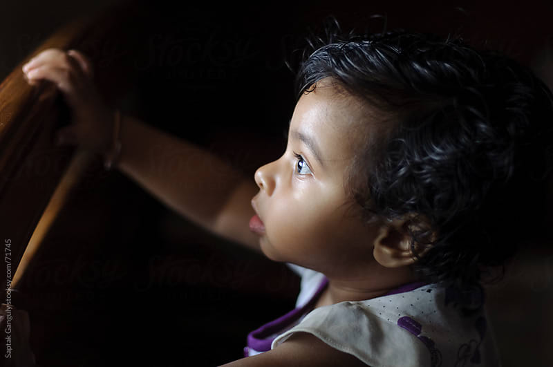 Baby girl staring at light in amazement by Saptak Ganguly for Stocksy United