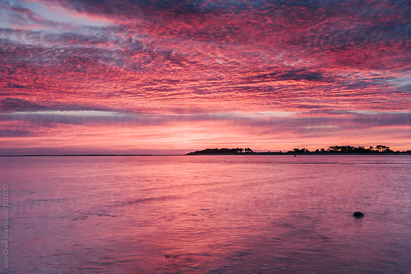 Pink dawn sky reflected in the surface of the sea. Norfolk, UK. by Liam Grant for Stocksy United