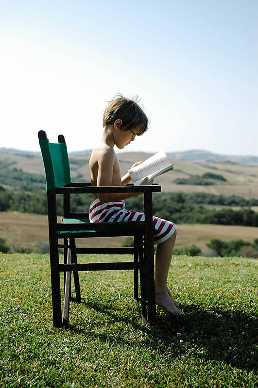 Boy reading a book on a hill in Tuscany by Kirstin Mckee for Stocksy United