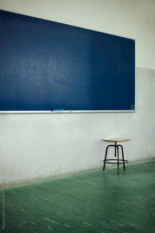 School blue blackboard in a green floor classroom by Miquel Llonch for Stocksy United