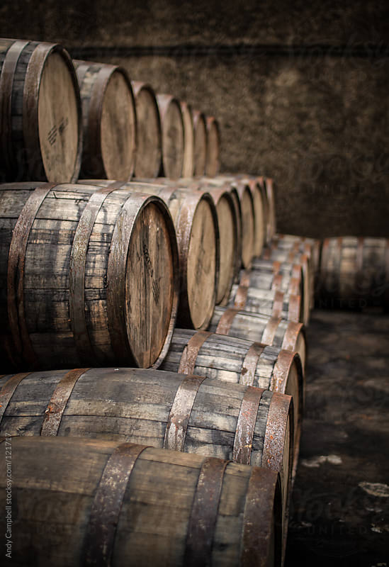 Wooden barrels and casks sit in a pile by Andy Campbell for Stocksy United