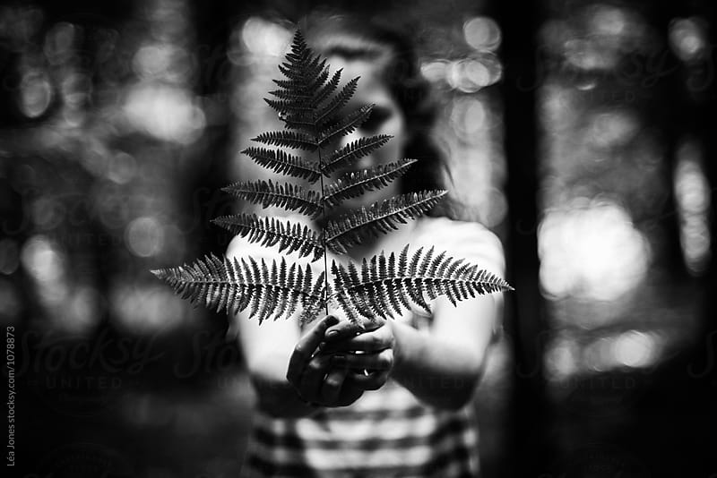 young woman holding a fern by Léa Jones for Stocksy United
