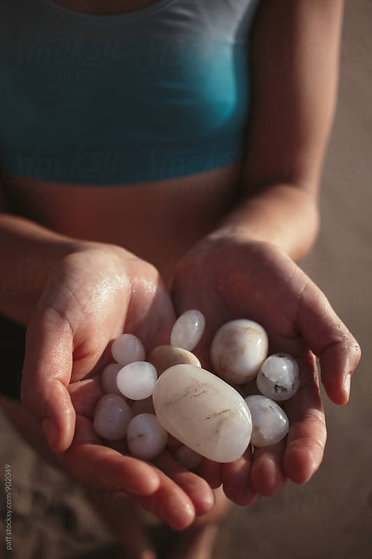 Tan girl holding seaglass stones in her hands on the beach by paff for Stocksy United