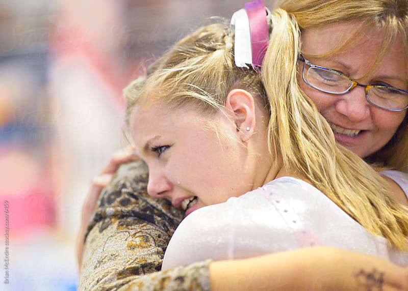 Mother hugs daughter after gymnastics performance by Brian McEntire for Stocksy United