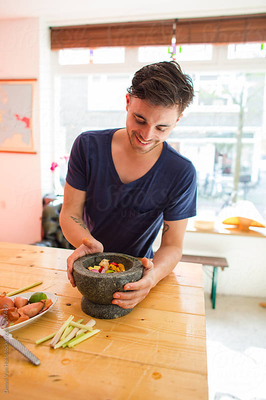 Young man cooking asian food with fresh ingredients by Denni Van Huis for Stocksy United