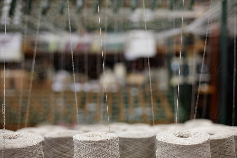 Close up of thread cones in a textile workshop by Miquel Llonch for Stocksy United