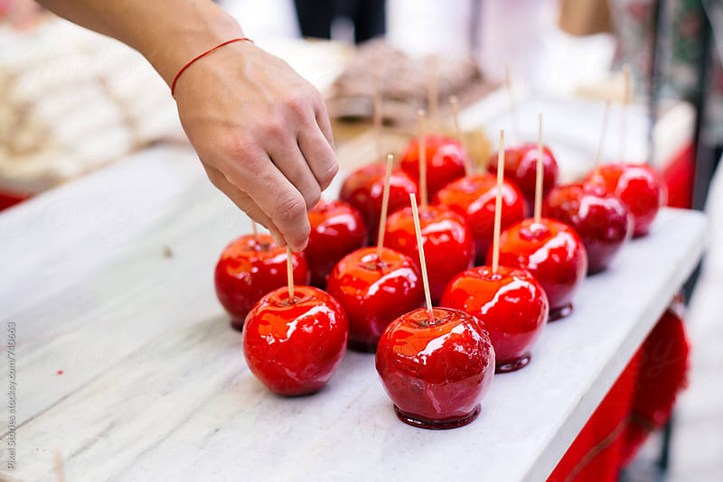Person placing just coated candy apples by Pixel Stories for Stocksy United