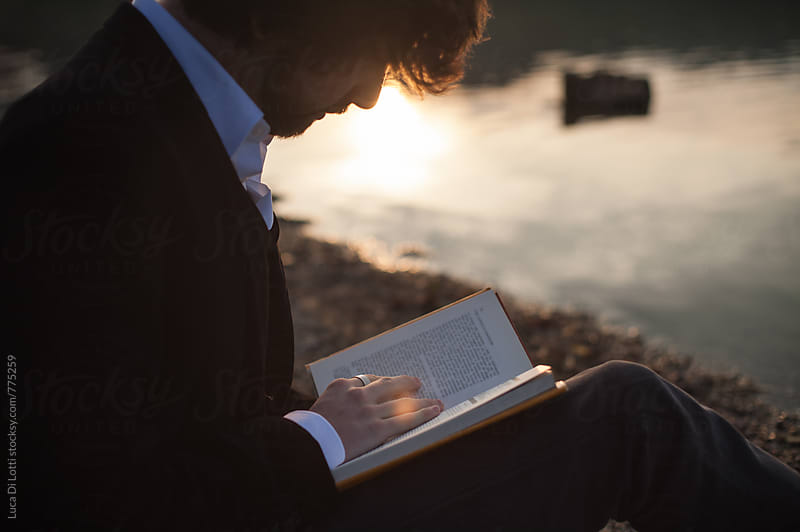 Young handsome bearded man reading a book by a lake during sunset by Luca Di Lotti for Stocksy United