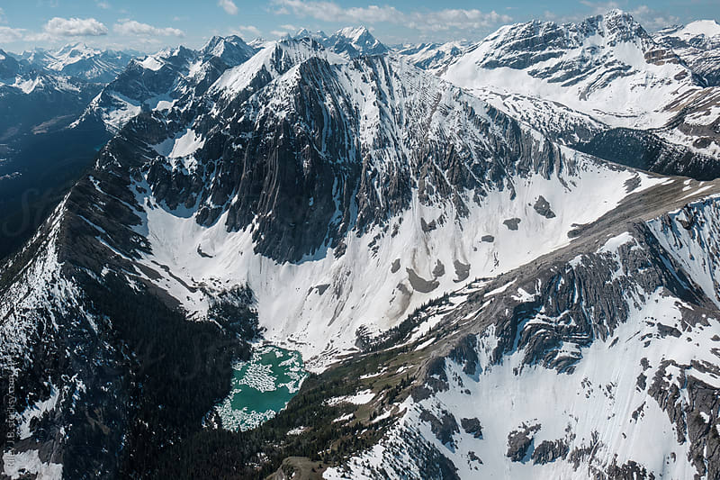 Vivid blue glacial lake at the bottom of a mountain by Riley J.B. for Stocksy United