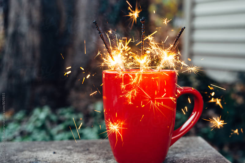lit sparklers in a red ceramic cup by Gabriel (Gabi) Bucataru for Stocksy United