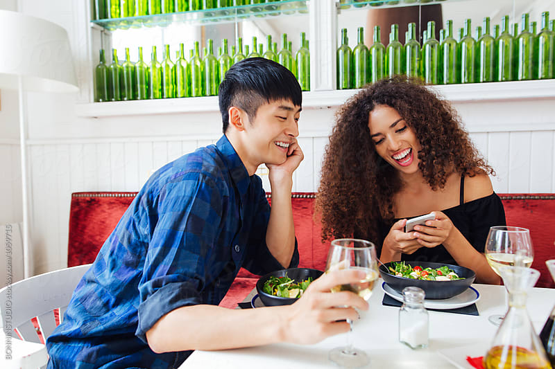 Smiling woman taking a photo of her salad whilst eating with her boyfriend in a restaurant.  by BONNINSTUDIO for Stocksy United