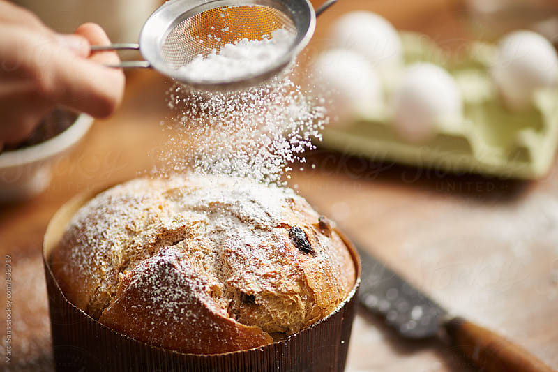Man's hand powdering panettone with sugar using sifter by Martí Sans for Stocksy United
