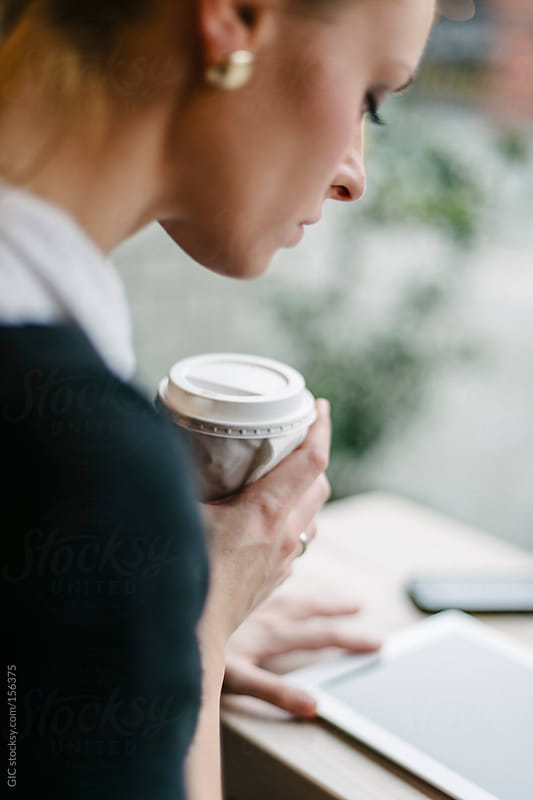 Young woman holding a cup of coffee sitting at cafe by GIC for Stocksy United