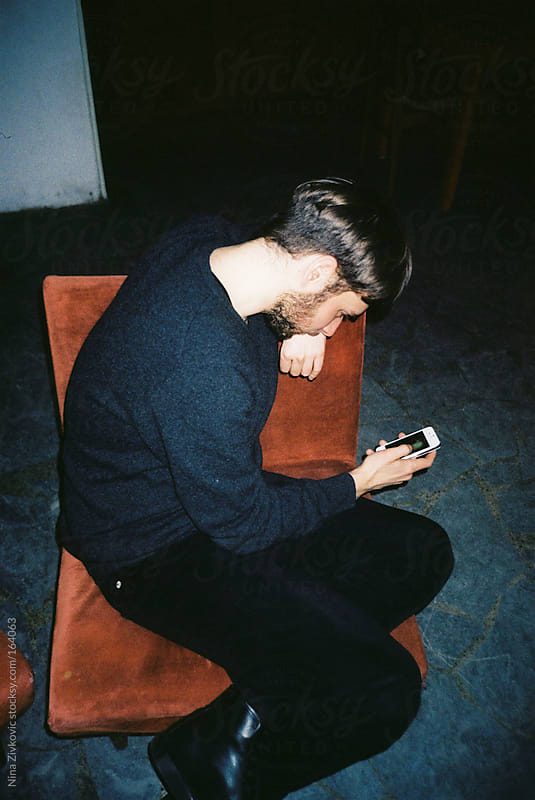 A young man using his phone. by Nina Zivkovic for Stocksy United