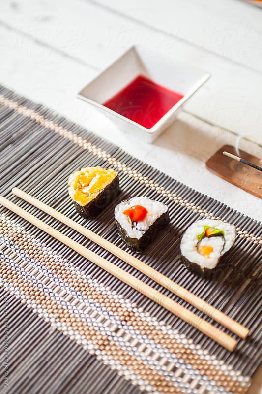 Sushi rolls with sauce and chopsticks. by Audrey Shtecinjo for Stocksy United