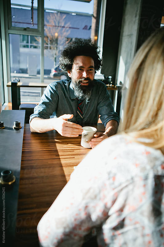 Latin man smiling while chatting with a woman over coffee by Kristine Weilert for Stocksy United