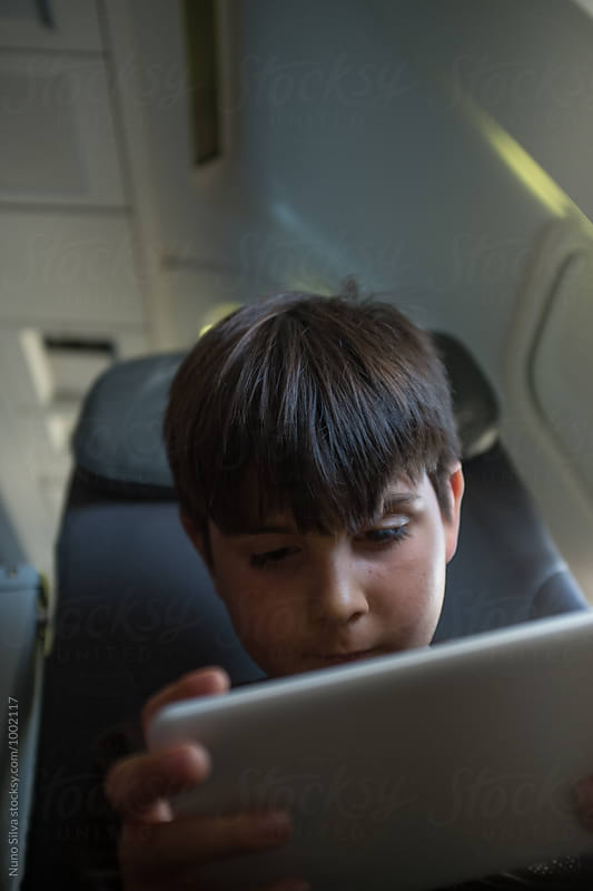 Using a tablet on an airplane. by Nuno Silva for Stocksy United