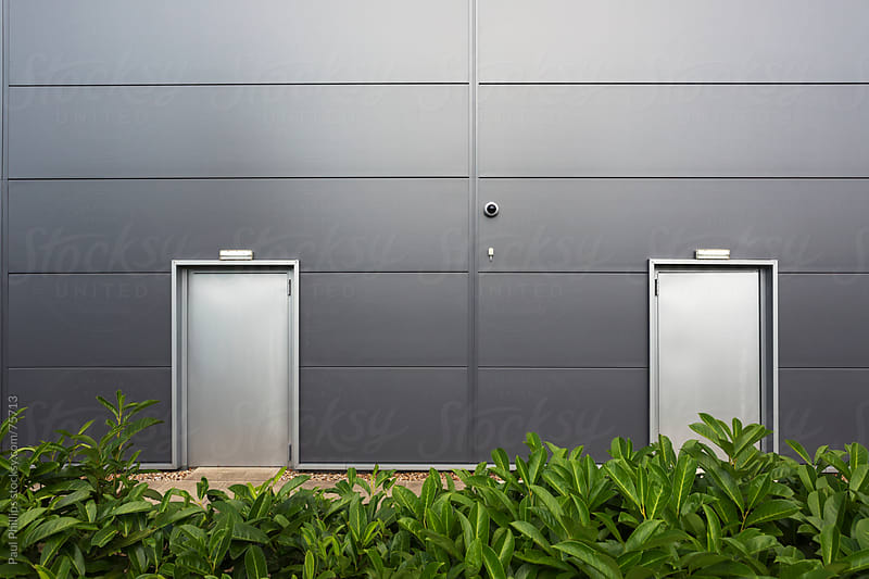 Steel doors at the entrance to a grey warehouse by Paul Phillips for Stocksy United