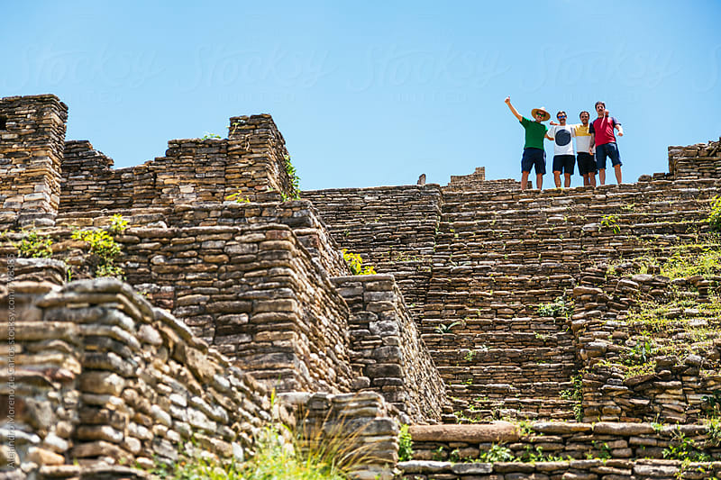 Four friends at the top of ancient pre-columbian ruins on a sunny day during their vacation travel by Alejandro Moreno de Carlos for Stocksy United