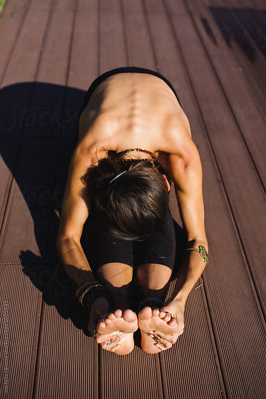 Woman doing yoga pose: Paschimottanasana by michela ravasio for Stocksy United