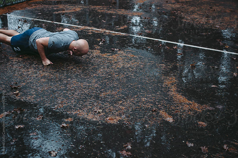 Man doing push-ups on fists on wet ground outside by Rob and Julia Campbell for Stocksy United