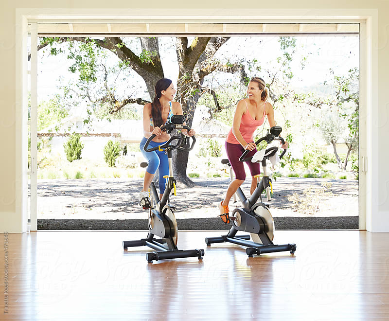 Friends Working Out On Exercise Bike At Resort Health Club by Trinette Reed for Stocksy United