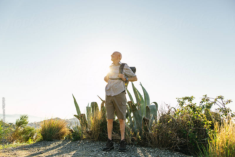 Senior man enjoying a sunny day on the mountain. by BONNINSTUDIO for Stocksy United