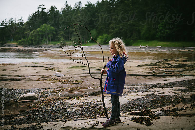 Little girl stands on beach with a large stick in her hand looking out to the ocean. by Cherish Bryck for Stocksy United